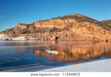 winter canoeing in Colorado - senior male paddling a decked expedition canoe, Horsetooth Reservoir near Fort Collins, Colorado in winter scenery