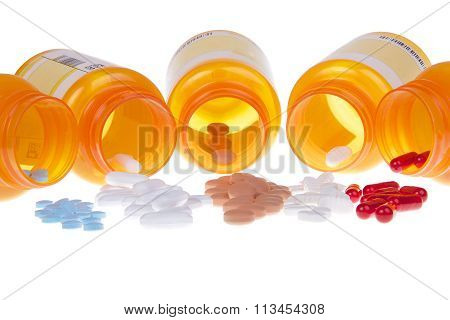 Five prescription bottles with pills spilling out on table isolated