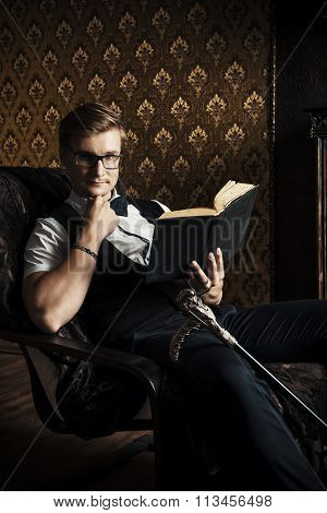 Handsome well-dressed man sitting by the fireplace in a room with classic vintage interior and reading a book. Fashion. Luxury.