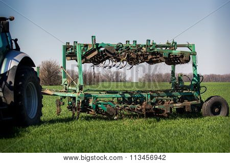 Weeding-machine Behind Tractor On Green Wheat Field