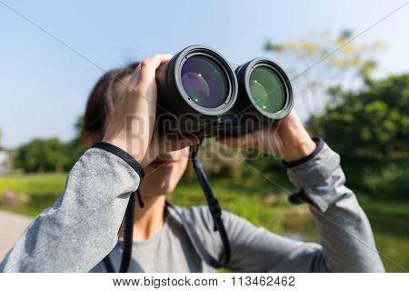 Asian Woman looking though binoculars