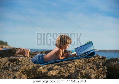 Little Boy Reading On The Beach