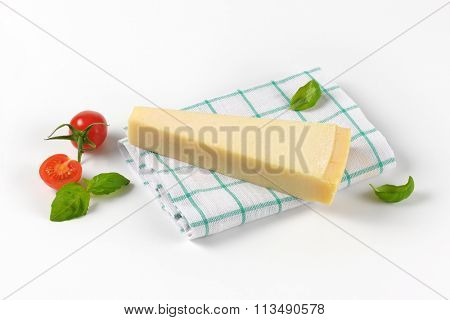 wedge of fresh parmesan cheese and cherry tomatoes on checkered dishtowel