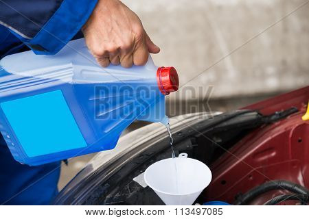 Serviceman Pouring Windshield Washer Fluid Into Car