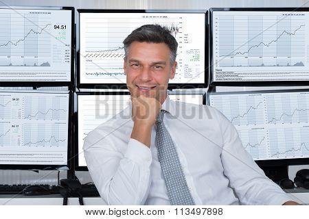 Confident Stock Market Broker Leaning On Desk