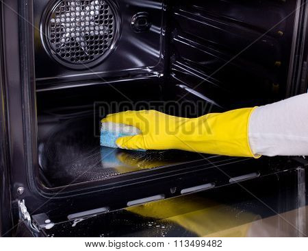 Close up of female hand with yellow protective gloves cleaning oven poster