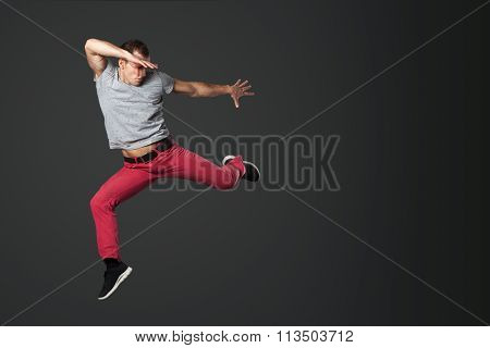 Young Male Dancer Jumping In Studio.