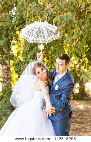 Just married couple holding white umbrella