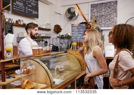 Young Women Friends Placing An Order In A Coffee Shop
