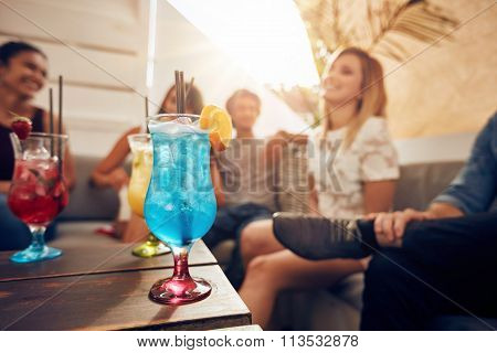 Cocktails On Table With Young People Partying On Rooftop