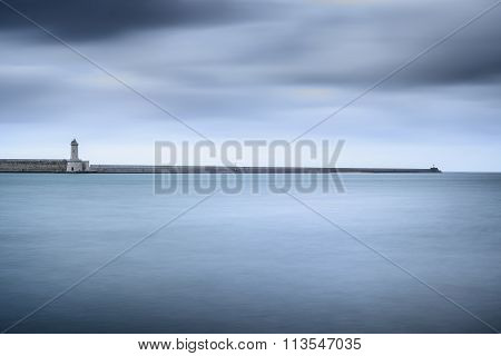 Livorno Port Lighthouse, Breakwater And Soft Water Under Cloudy Sky