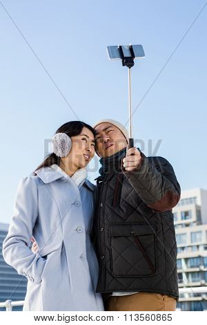 Couple making face and clicking pictures using selfie stick against building