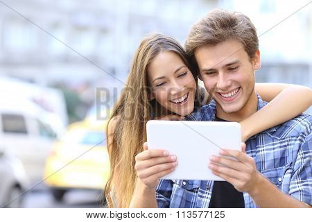 Happy Couple Sharing A Tablet In The Street