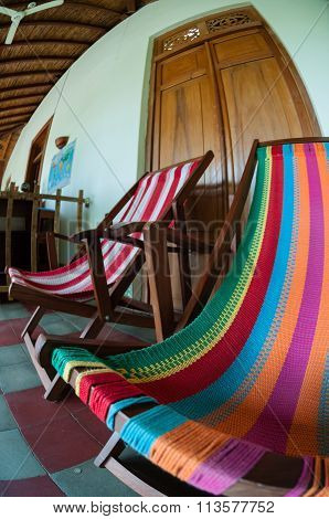 Colorful deck chair in front of a wooden door hostel Casa del poeta