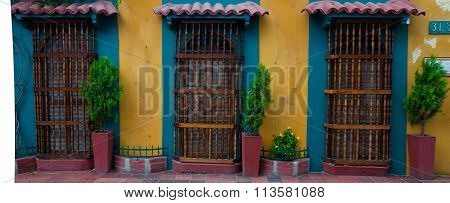 Yellow colonial house front with three doors