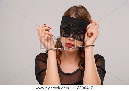 Sexual woman in eyeshade locked with handcuffs.