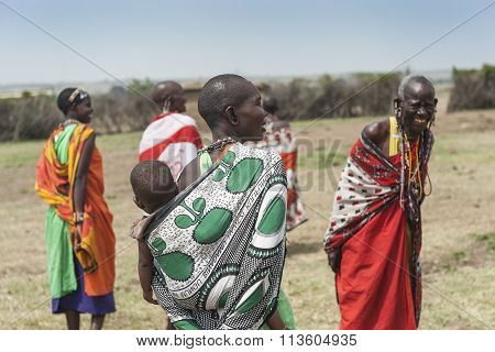 MASAI MARA, KENYA - FEB 2015 - Tribe woman carries child in colorful textile.