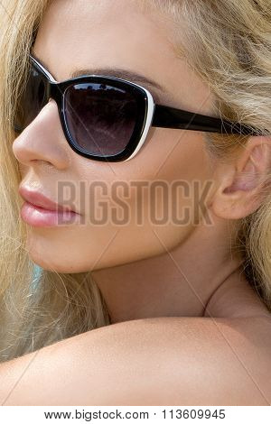 Beautiful blond hair sexy woman young girl model in sunglasses and elegant white and black sexy swimsuit lingerie with crystals around the pool with a balustrade overlooking the sea and the island of Santorini