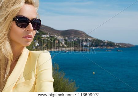 Beautiful blond hair sexy woman young girl model in sunglasses in yellow elegant jacket suit around the pool with a balustrade overlooking the sea and the island of Santorini