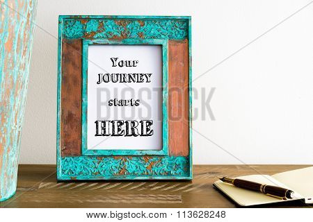 Vintage Photo Frame On Wooden Table With Text Your Journey Starts Here