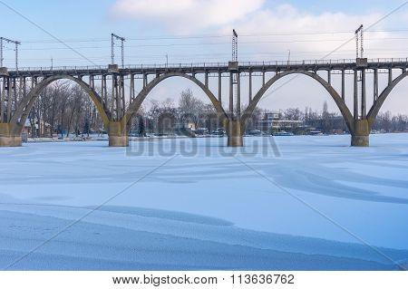Arched bridge on winter river Dnepr