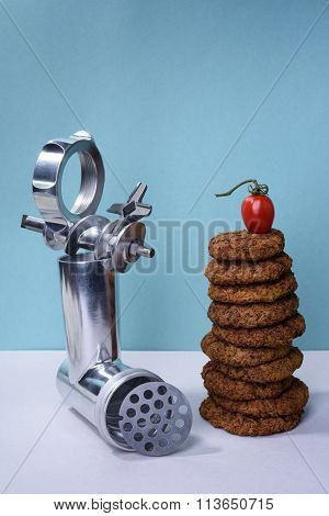 Burger beef steak cutlets and meat mincer on turquoise background.