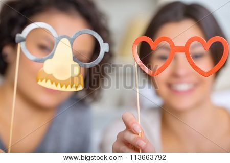 Two sisters showing funny party masks.