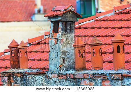 Architecture Details Of The House With Old Chimneys And Tile Roof On The Background