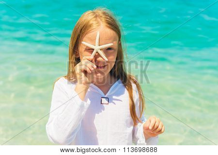 Cute little girl playing with a starfish on the beach on a very hot sunny day