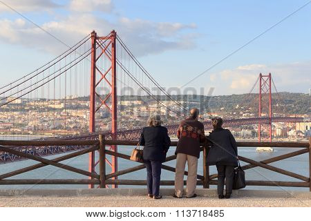 Old people looking on the 25 de Abril Bridge and Lisbon cityscape