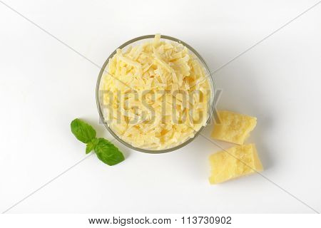 bowl of grated parmesan cheese on white background