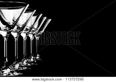 Row of empty martini glasses on black background in horizontal format