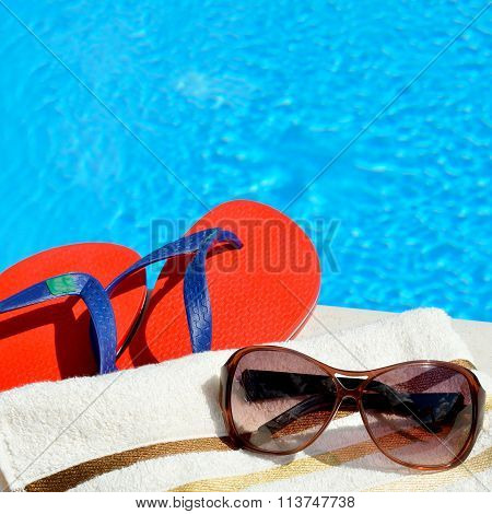 Sunglasses beach towel and flip-flops by the swimming pool. poster