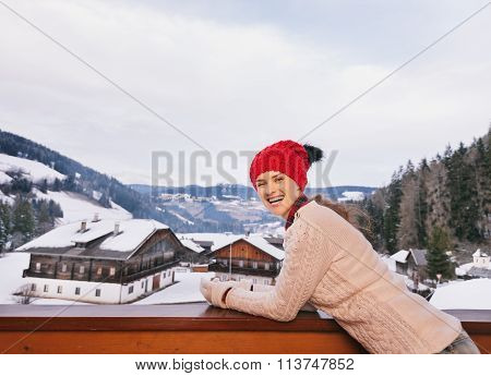 Smiling Woman On Balcony Overlooking The Snow-capped Mountains