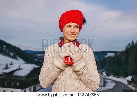 Woman With Red Cup On Balcony Overlooking Mountains In Evening