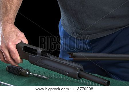 Gunsmith disassembling and reassembling 20 gauge pump action shotgun