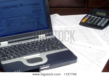 Laptop And Tax Return On Desk