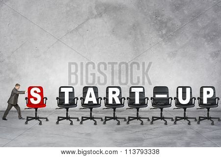 Young businessman pushing word start-up