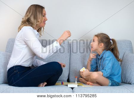 Mother And Daughter Playing Board Game At Home.