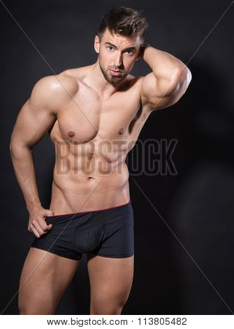handsome young and fit bodybuilder posing shirtless