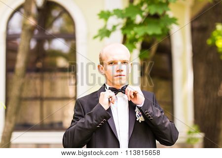 The groom holds a tie and smiles.