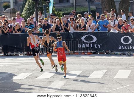 Audience Clapping Hands For Group Of Running Triathletes