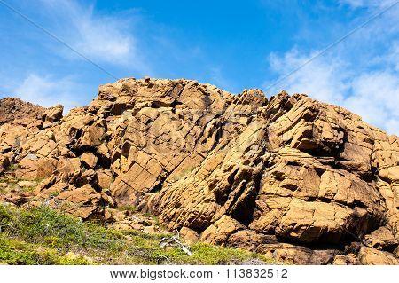 Large Irregular Cracked Rock Outcrop Against Sky