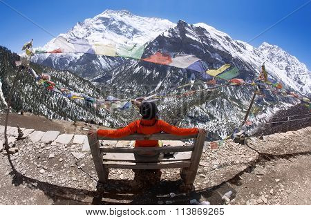 A young woman is sitting on a bench enjoying a beautiful view of the mountains.
