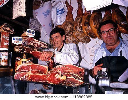 Butchers carving cured ham, Toledo.