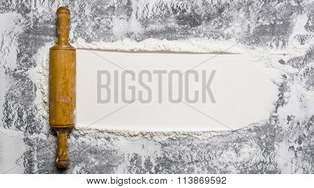 Preparation Of The Dough. The Rolling Pin With Flour On A Stone Background.