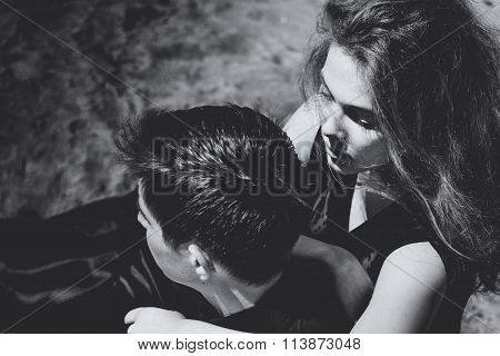 Beautiful couple. Girl whispers something in the ear of young man, black and white portrait