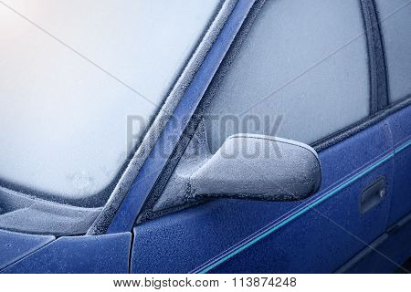 Car window and side mirror covered with ice in the morning
