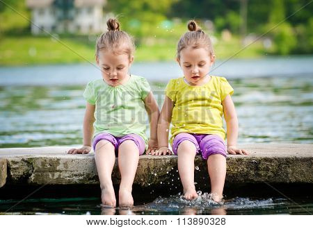 Twin Girls Exercising On A Lake Shore