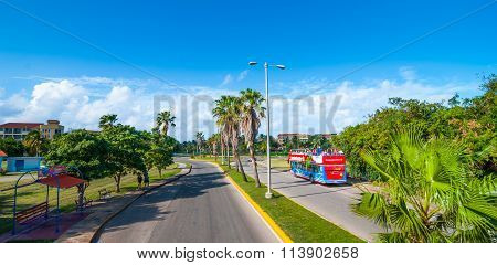 Bus tour of Varadero, Cuba.   Sunny morning - vibrant red colored bus takes tourists into town.